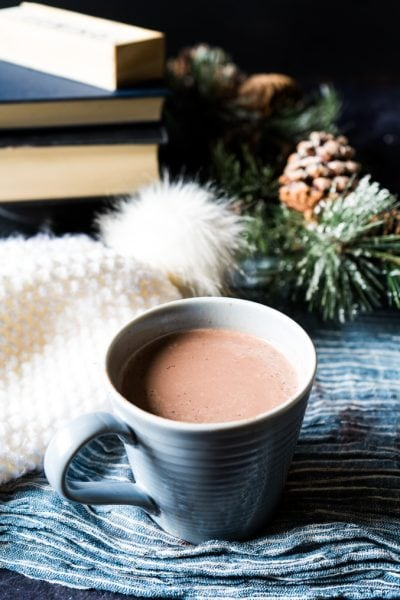 A mug of low-carb hot chocolate beside a winter hat and books