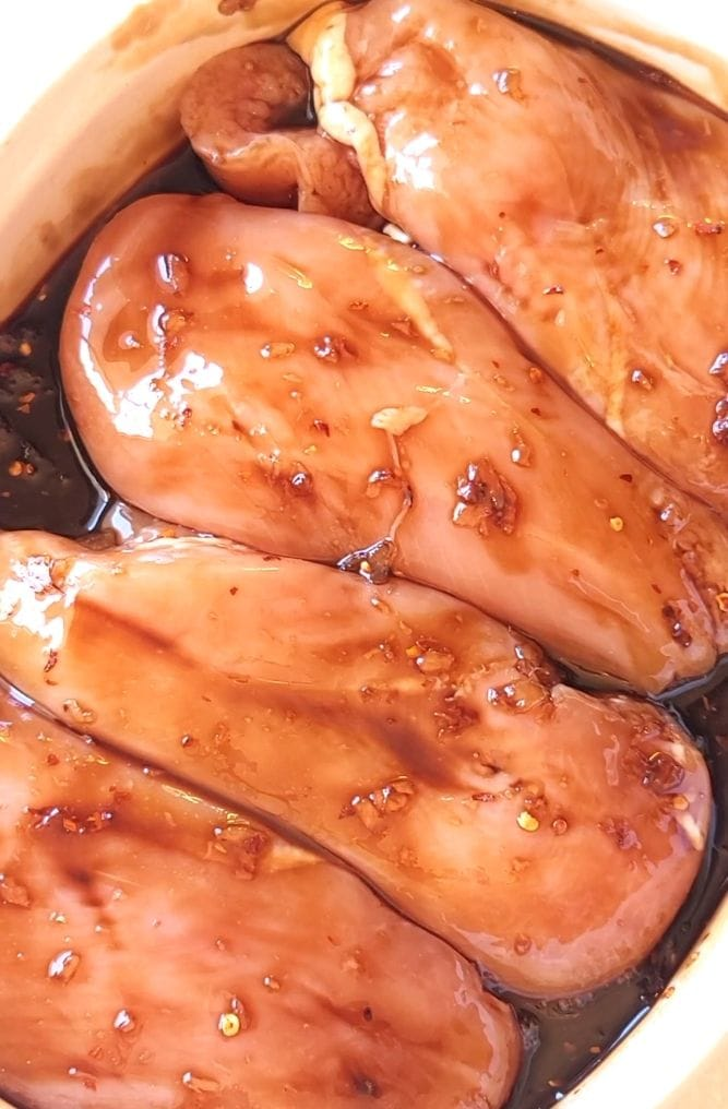 Marinated chicken breasts in a baking dish.