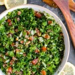 A large bowl of tabbouleh salad on a table with salad tongs and lemons
