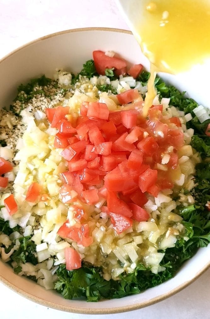 Tabouli salad dressing being poured over a salad.
