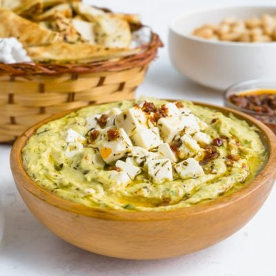 Cannellini bean dip made with harissa in a wooden bowl topped with feta