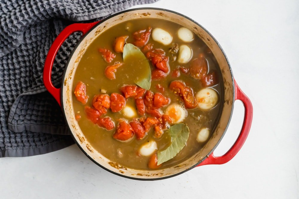 A dutch oven filled with tomatoes and other stew ingredients