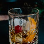 An old-fashioned cocktail on a black background