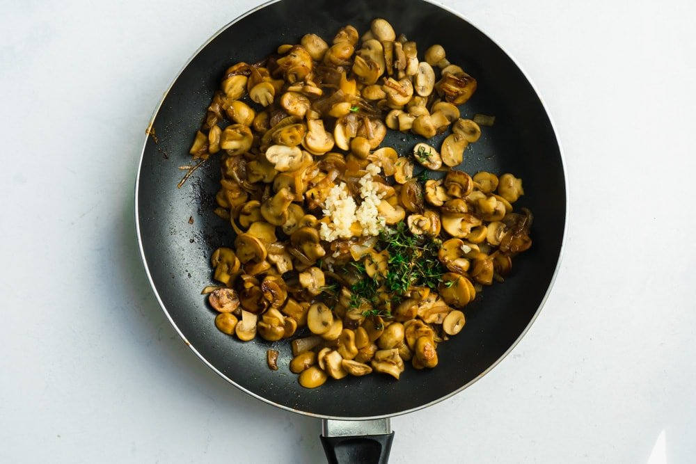 a pan of browned mushrooms, garlic and thyme