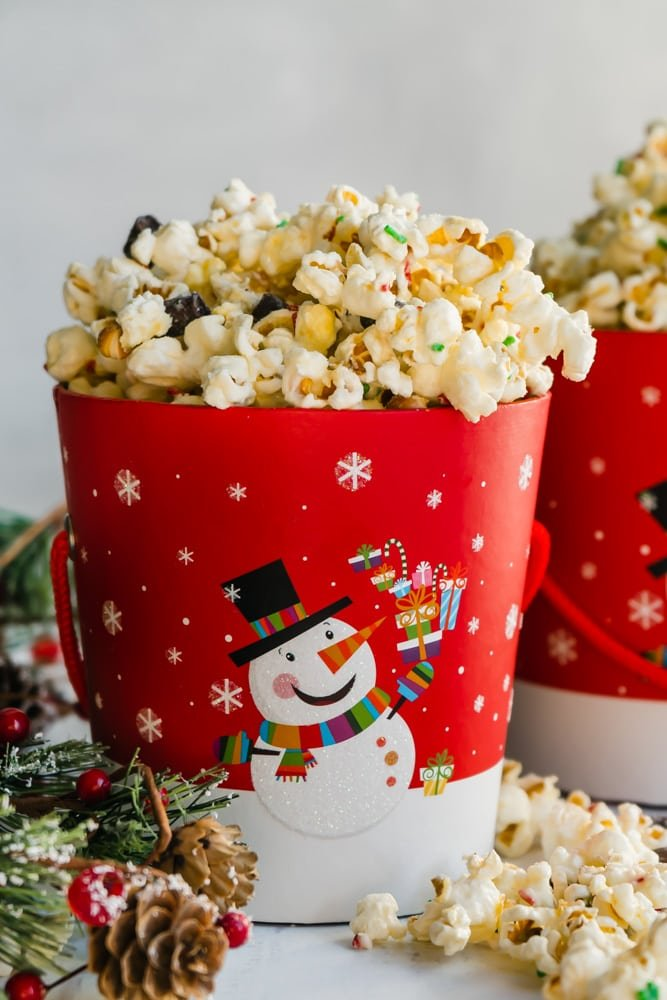 A bucket of holiday popcorn with sprinkles and dark chocolate