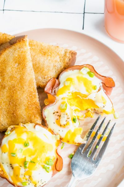 An egg cup cut open with a fork with some toast.