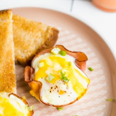A baked egg cup topped with green onions with a side of toast