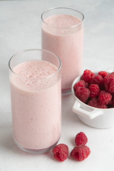 Two glasses from overhead filled with a green tea smoothie made with raspberries