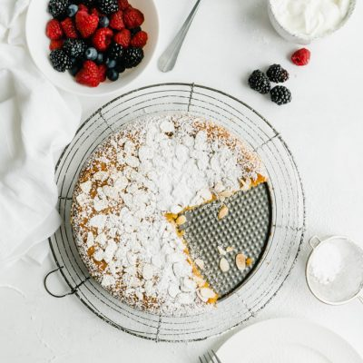 An overhead shot of an almond cake with two slices cut from it with berries and yogurt