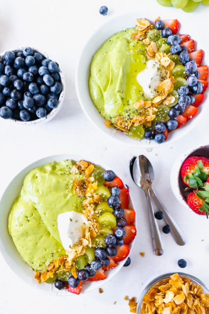 Two smoothie bowls on a white table surrounded by fruit