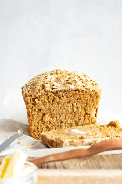 A loaf of beer bread made without yeast facing forward with one slice off.