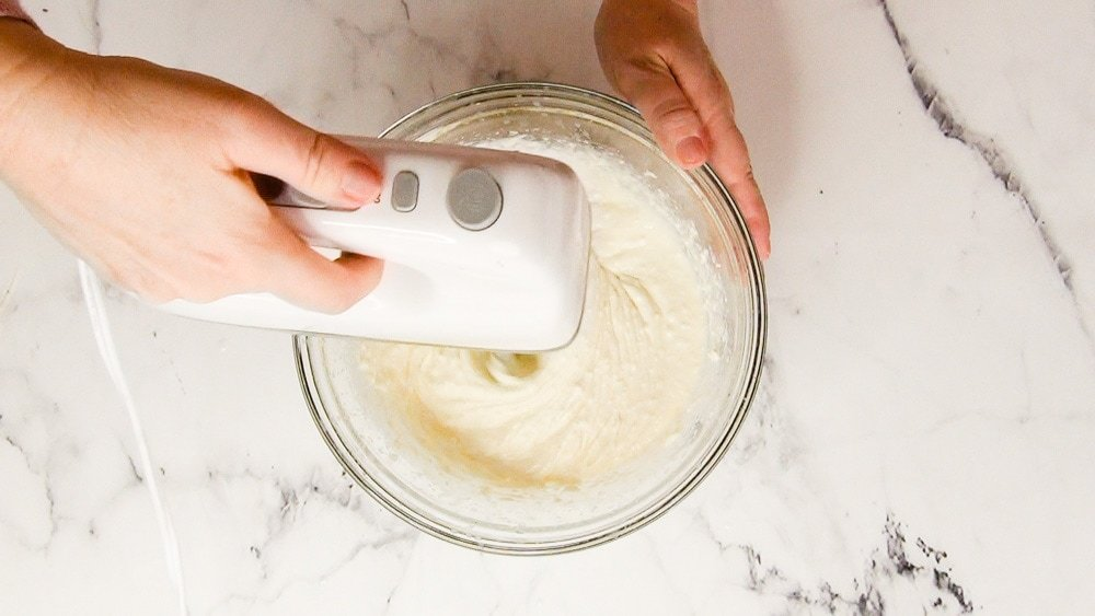 cream cheese being beaten with a hand-mixer