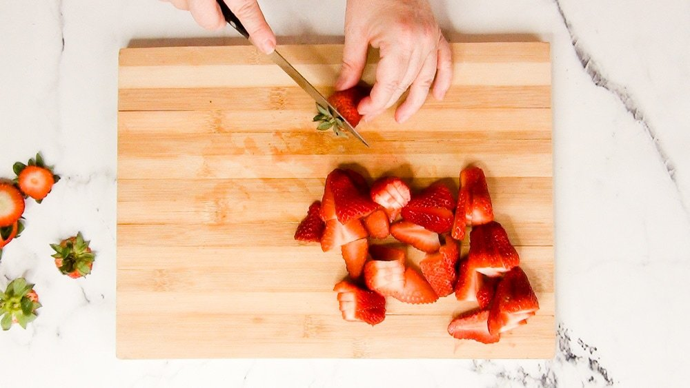 strawberries being sliced on a bamboo cutting board