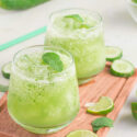 Two glasses filled with a frozen cucumber mojito recipe