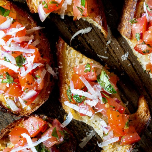 Close up of pieces of bruschetta topped with shaved parmesan on a cutting board