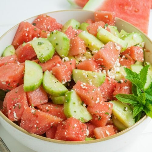 A cucumber and watermelon salad in a white bowl.