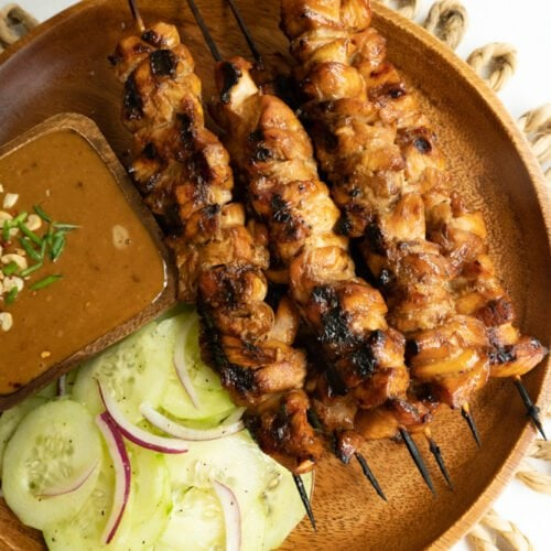 Grilled chicken satay recipe shown on a plate with salad and dipping sauce.