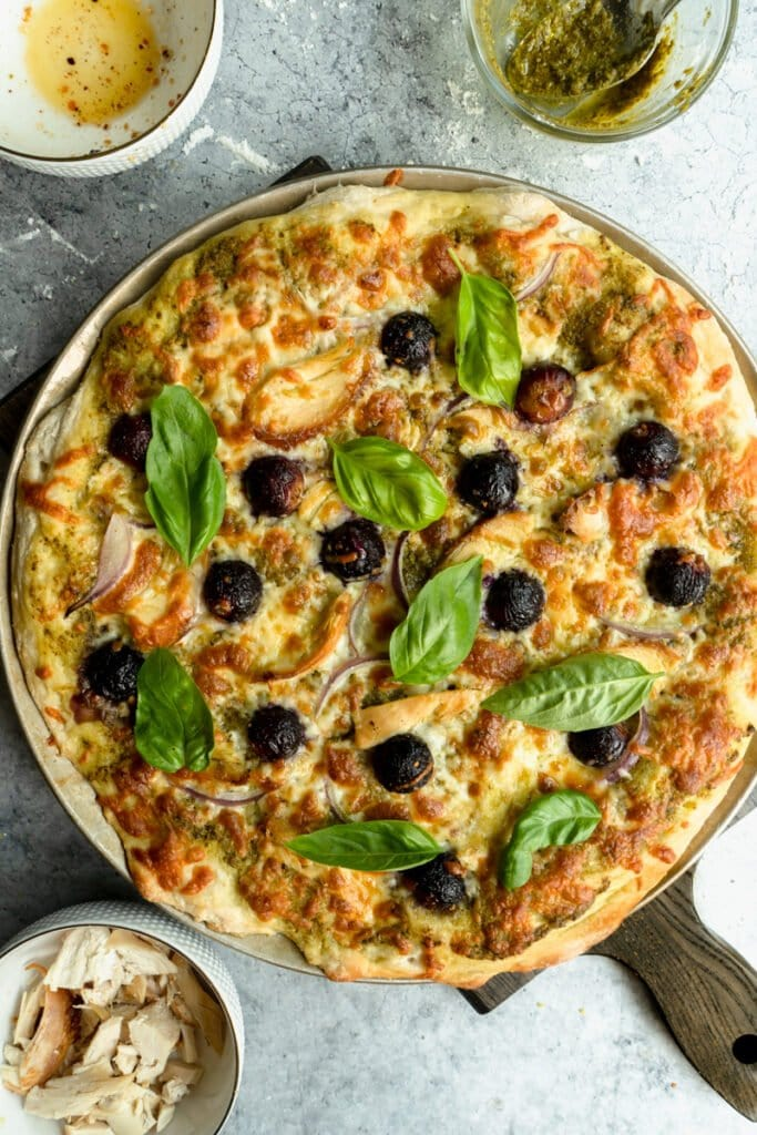 A Chicken pizza made with pesto, mozzarella, grapes and red onion and topped with basil.