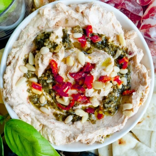 A close up of a pesto and cream cheese dip topped with sundried tomatoes and pesto