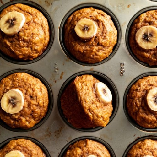 A muffin tin filled with a recipe for whole what pumpkin muffins.