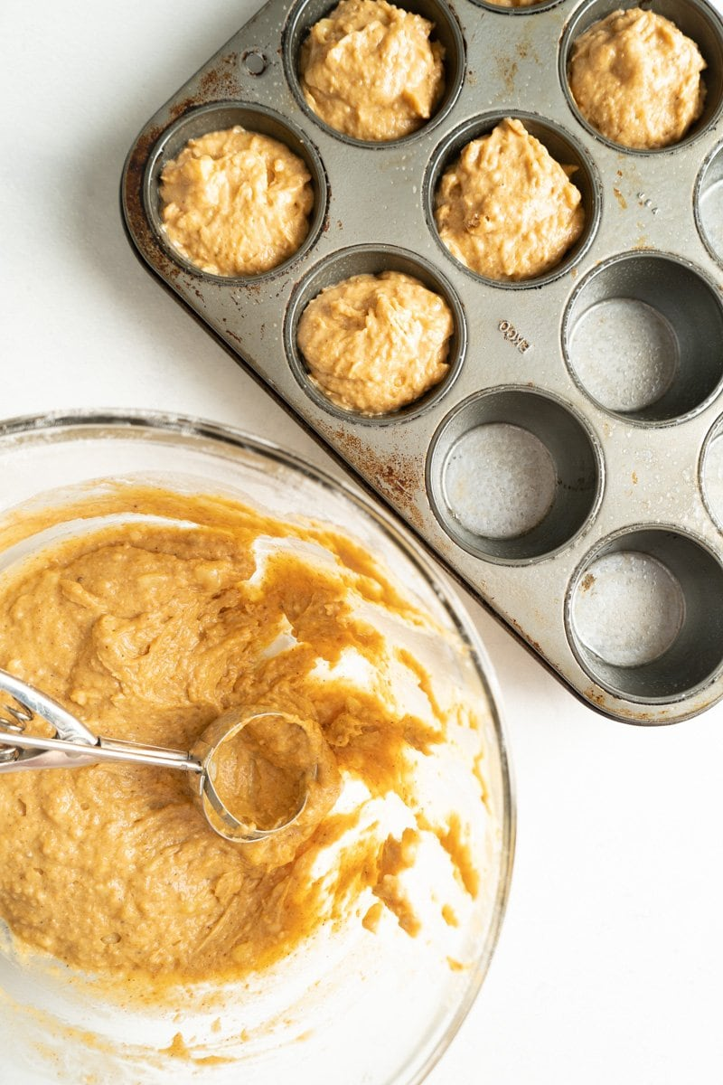 Batter for an easy banana pumpkin muffin recipe being scooped into a tin.